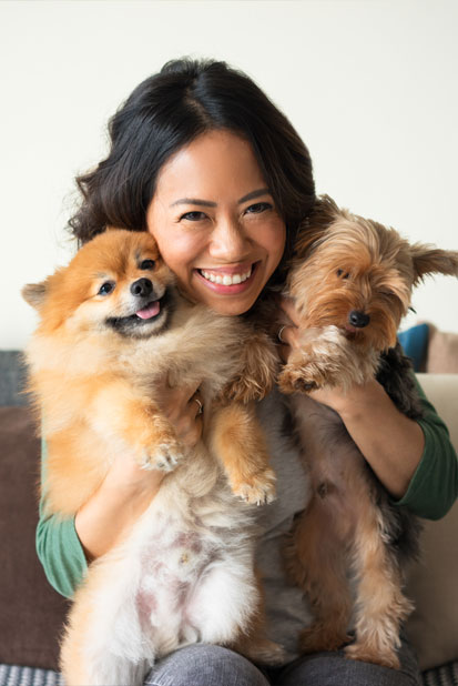 Woman hugging two small dogs